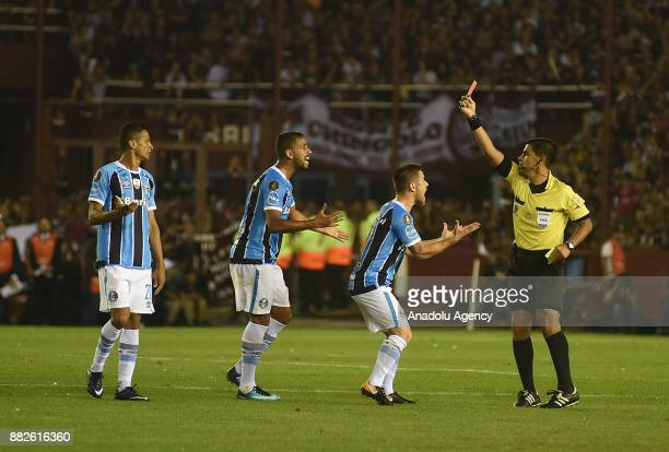 Ramiro Benettii of Gremio is being sent off with a red card by referee Enrique Caceres during Copa Libertadores final match between Lanus and Gremio...