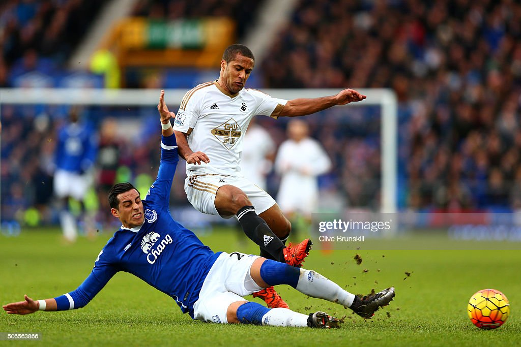 Ramiro Funes Mori of Everton slides in on Wayne Routledge of Swansea City during the Barclays Premier League match between Everton and Swansea City at Goodison Park on January 24, 2016 in Liverpool, England.