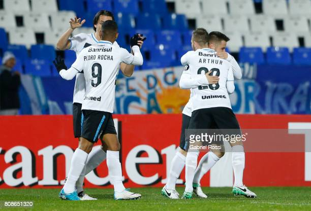 Ramiro of Gremio celebrates with teammates Pedro Rocha and Arthur after scoring the opening goal of his team during a first leg match between Godoy...
