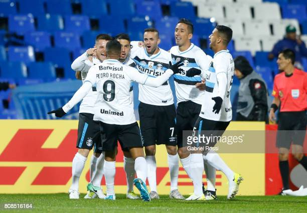 Ramiro of Gremio celebrates with teammates Pedro Rocha Luan and Lucas Barrios after scoring the opening goal of his team during a first leg match...