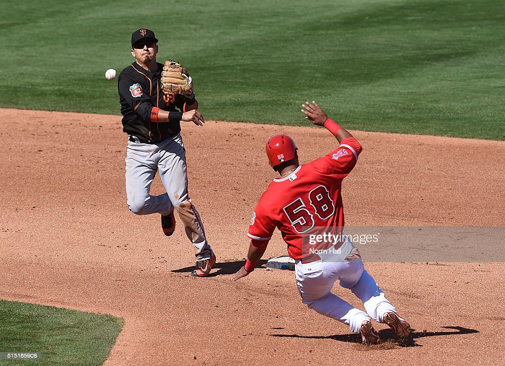 Ramiro Pena #1 of the San Francisco Giants turns a double play as Carlos Perez #58 of the Los Angeles Angels of Anaheim slides into second base during the fourth inning at Tempe Diablo Stadium on March 12, 2016 in Tempe, Arizona.