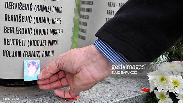 Ramiz Holjan father of tragically killed child Admir Holjan leaves a photo of his son near a monument bearing the names of children killed during the...