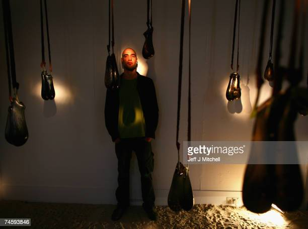 Ramon Beaskoetxea a BA honours student, at Edinburgh college of Art, stands with his art installation of hanging glass bulls testicles June 15, 2007...