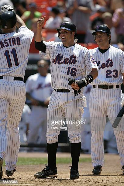 Ramon Castro of the New York Mets is greeted by Doug Mientkiewicz and Kazuhisa Ishii during the game against the San Diego Padres at Shea Stadium on...
