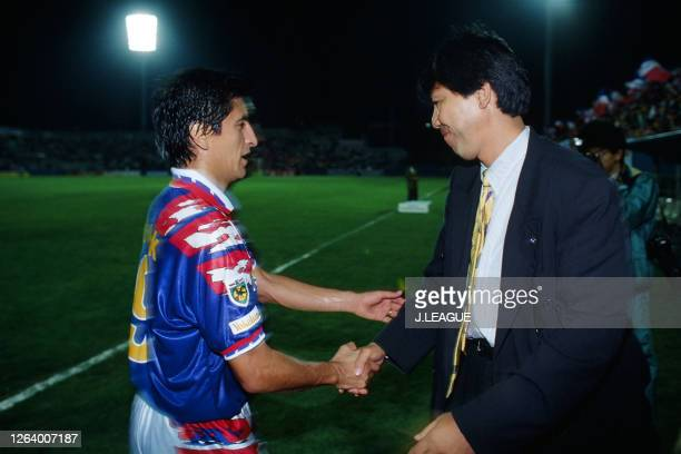 Ramon Diaz and head coach Hidehiko Shimizu of Yokohama Marinos shake hands after their 1-0 victory in the J.League Suntory Series match between...