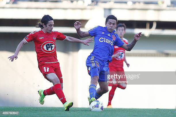Ramon Fernandez of Universidad de Chile fights for the ball with Jonathan Cisternas of Nublense during a match between Nublense and Universidad de...