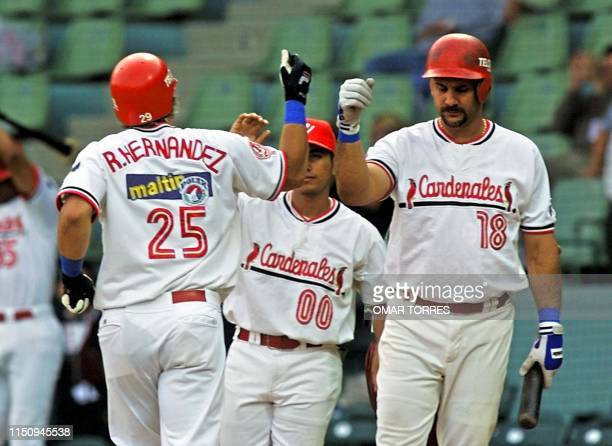 Ramon Hernandez catcher of the Cardenales de Lara of Venezuela is saluted by first baseman Luis Raven after hitting a homerun 07 Febraury 2001 in...