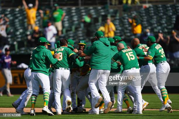 Ramon Laureano of the Oakland Athletics celebrates with his teammates after reaching first on an error to walk off in the tenth inning against the...