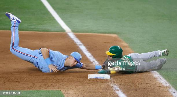 Ramon Laureano of the Oakland Athletics is caught stealing and is tagged out at first base by Nate Lowe of the Texas Rangers during the eighth inning...