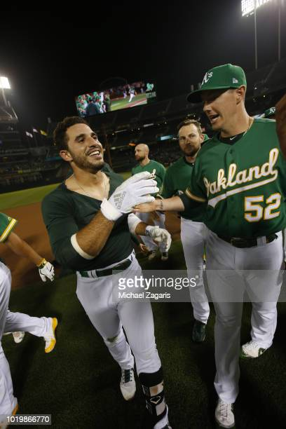 Ramon Laureano of the Oakland Athletics is congratulated by Ryan Buchter after hitting a walkoff single following the game against the Detroit Tigers...