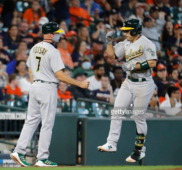 Ramon Laureano of the Oakland Athletics is congratulated by third base coach Mark Kotsay after a two run home run in the fifth inning against the...