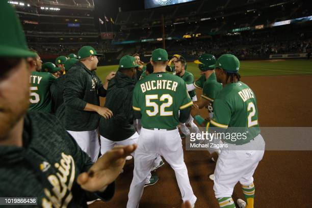Ramon Laureano of the Oakland Athletics is mobbed by teammates after hitting a walkoff single following the game against the Detroit Tigers at the...