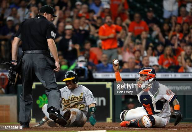 Ramon Laureano of the Oakland Athletics is tagged out by Martin Maldonado of the Houston Astros shows umpire Chris Conroy the ball in the sixth...