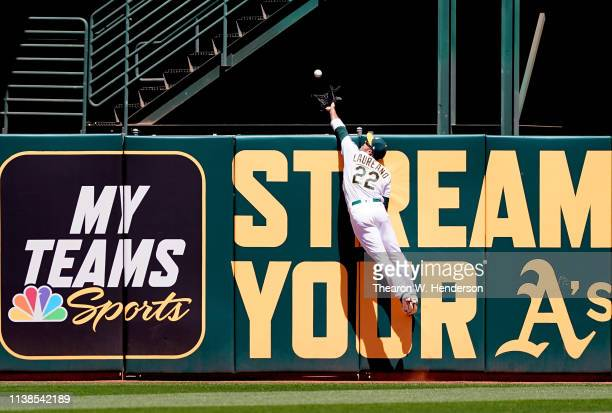 Ramon Laureano of the Oakland Athletics leaps at the wall to take a home run away from Teoscar Hernandez of the Toronto Blue Jays in the top of the...
