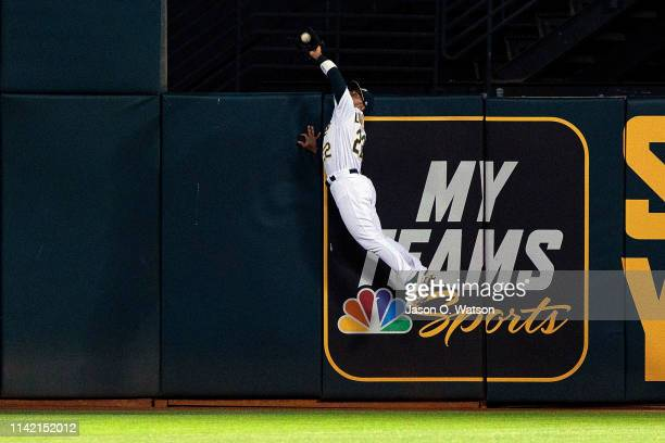 Ramon Laureano of the Oakland Athletics leaps for and catches a fly ball hit off the bat of Joey Votto of the Cincinnati Reds during the sixth inning...
