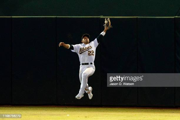 Ramon Laureano of the Oakland Athletics leaps for but is unable to catch a fly ball hit off the bat of Whit Merrifield of the Kansas City Royals...
