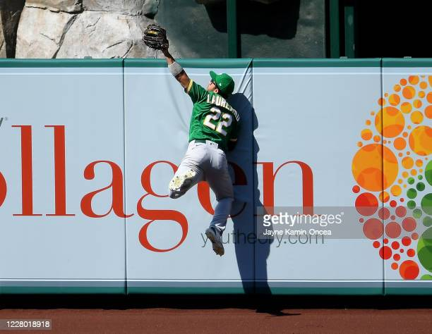 Ramon Laureano of the Oakland Athletics reaches over the wall to steal a home run from Brian Goodwin of the Los Angeles Angels in the eighth inning...