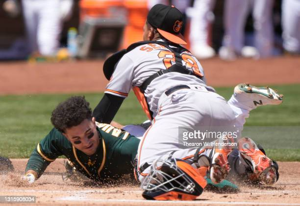 Ramon Laureano of the Oakland Athletics scores sliding under Pedro Severino of the Baltimore Orioles in the first inning at RingCentral Coliseum on...