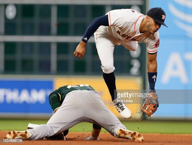 Ramon Laureano of the Oakland Athletics slides under the tag attempt by Carlos Correa of the Houston Astros in the fourth inning at Minute Maid Park...