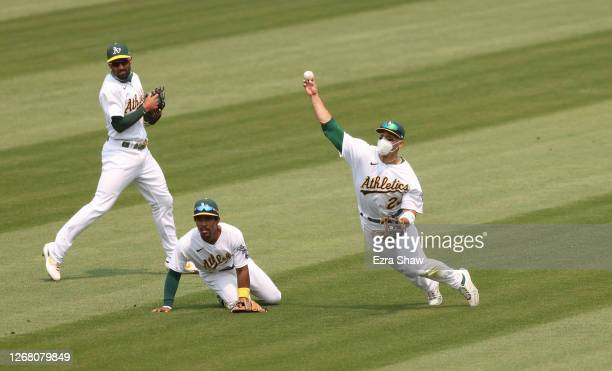 Ramon Laureano of the Oakland Athletics throws the ball back in to second base as Tony Kemp and Marcus Semien look on in the third inning against the...