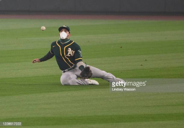 Ramon Laureano of the Oakland Athletics wears an N95-style mask as he catches a pop fly from Phillip Ervin of the Seattle Mariners in the second...