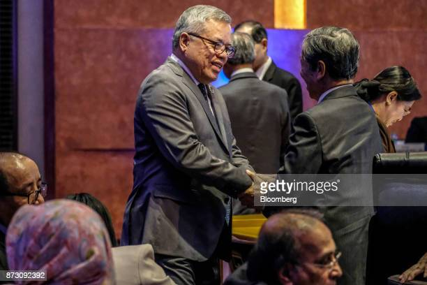 Ramon Lopez the Philippines' secretary of trade and industry left speaks with an attendee during the Asean economic council meeting at the...