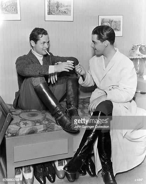 Ramon Novarro visits Robert Montgomery's dressing room for a cigarette