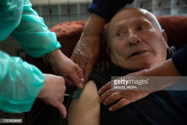 Ramon Quintana receives a dose of the Janssen vaccine against COVID-19 at his home in Taboadela during an in-house vaccination campaign for the...