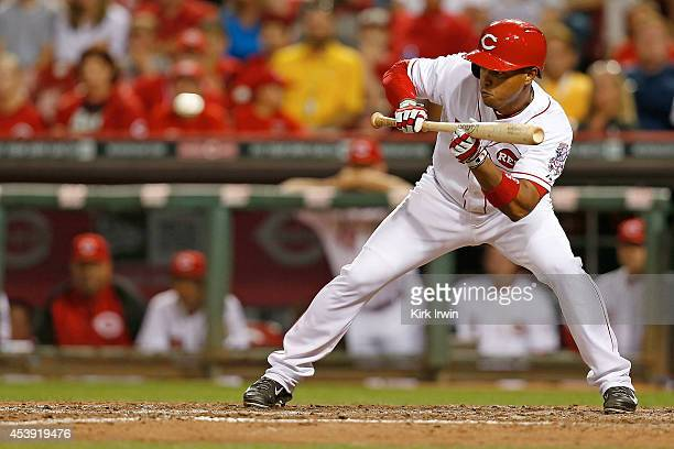 Ramon Santiago of the Cincinnati Reds attempts to bunt during the game against the Miami Marlins at Great American Ball Park on August 8 2014 in...