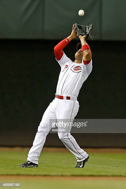 Ramon Santiago of the Cincinnati Reds catches a fly ball during the eighth inning against the Miami Marlins at Great American Ball Park on August 8...