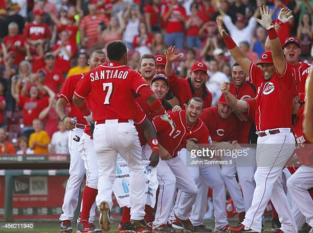 Ramon Santiago of the Cincinnati Reds celebrates his walk off grand slam home run with teammates in the 10th inning of play against the Pittsburgh...