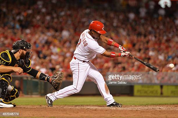 Ramon Santiago of the Cincinnati Reds hits an RBI single to tie the game in the eighth inning against the Pittsburgh Pirates at Great American Ball...