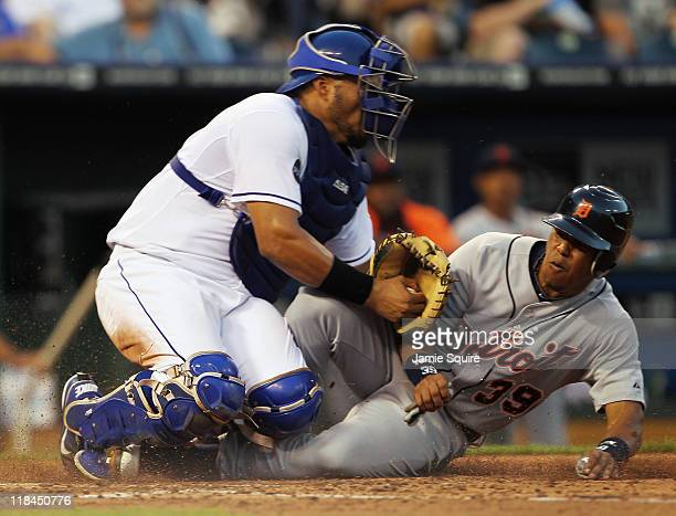 Ramon Santiago of the Detroit Tigers is tagged out at home plate by catcher Brayan Pena of the Kansas City Royals on a fielder's choice during the...