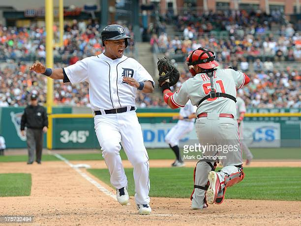 Ramon Santiago of the Detroit Tigers reacts after scoring a run ahead of the tag of Carlos Ruiz of the Philadelphia Phillies during the game at...