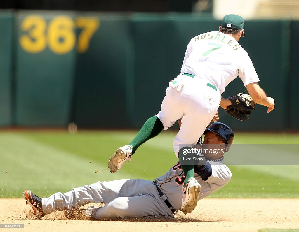 Ramon Santiago #39 of the Detroit Tigers slides in to second base while Adam Rosales #7 of the Oakland Athletics turns a double play at the Oakland-Alameda County Coliseum on May 20, 2010 in Oakland, California.