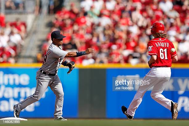 Ramon Santiago of the Detroit Tigers throws to first to turn a double play against Bronson Arroyo of the Cincinnati Reds at Great American Ball Park...
