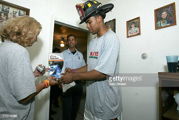 Ramon Sessions of the Milwaukee Bucks presents a new smoke detector to a resident as a tip off to Fire Prevention Week October 6 2007 in Milwaukee...