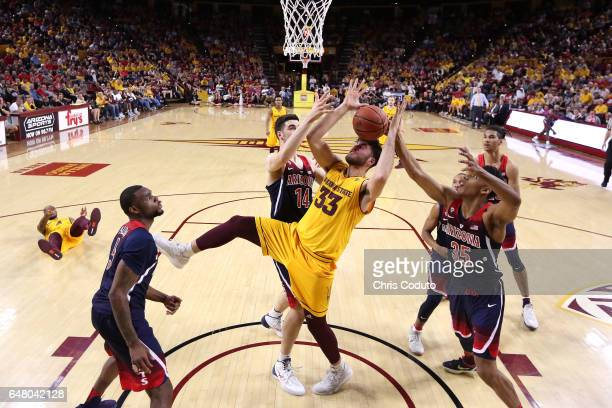 Ramon Vila of the Arizona State Sun Devils fights for a rebound with Dusan Ristic of the Arizona Wildcats and Allonzo Trier during the first half of...