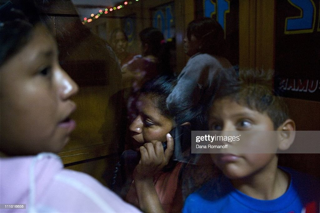 Ramona Aparicio Gonzales speaks with her husband and 17 year old son that illegally migrated to the United States in a phone booth at a call center on December 18, 2006 in Tasquillo. In the phone booth with her are her other children Ana Laura, 12 and Eduardo, nine. Her eldest son left seven months ago and her husband left four years ago and has not been able to return home. They both work in construction. Ramona cries: 'He left because the money doesn't reach. It's very sad, especially for the kids. They ask when dad is coming home and where he is. Perhaps this [their father being in the U.S.] can give them more now economically but they are missing his care.'