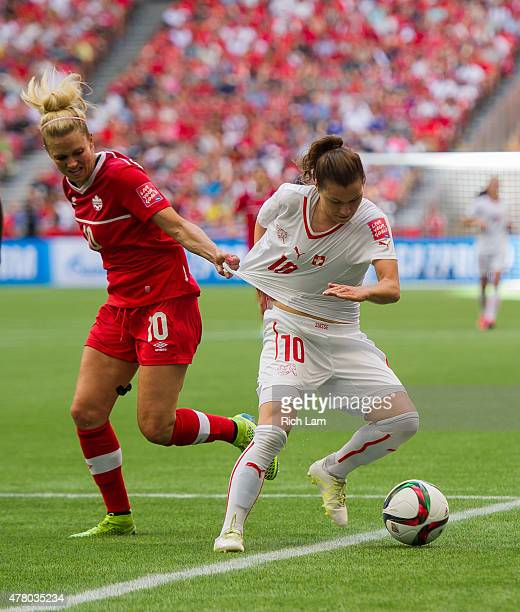 Ramona Bachmann of Switzerland has her jersey pulled by Lauren Sesselmann of Canada while trying to break free during the FIFA Women's World Cup...