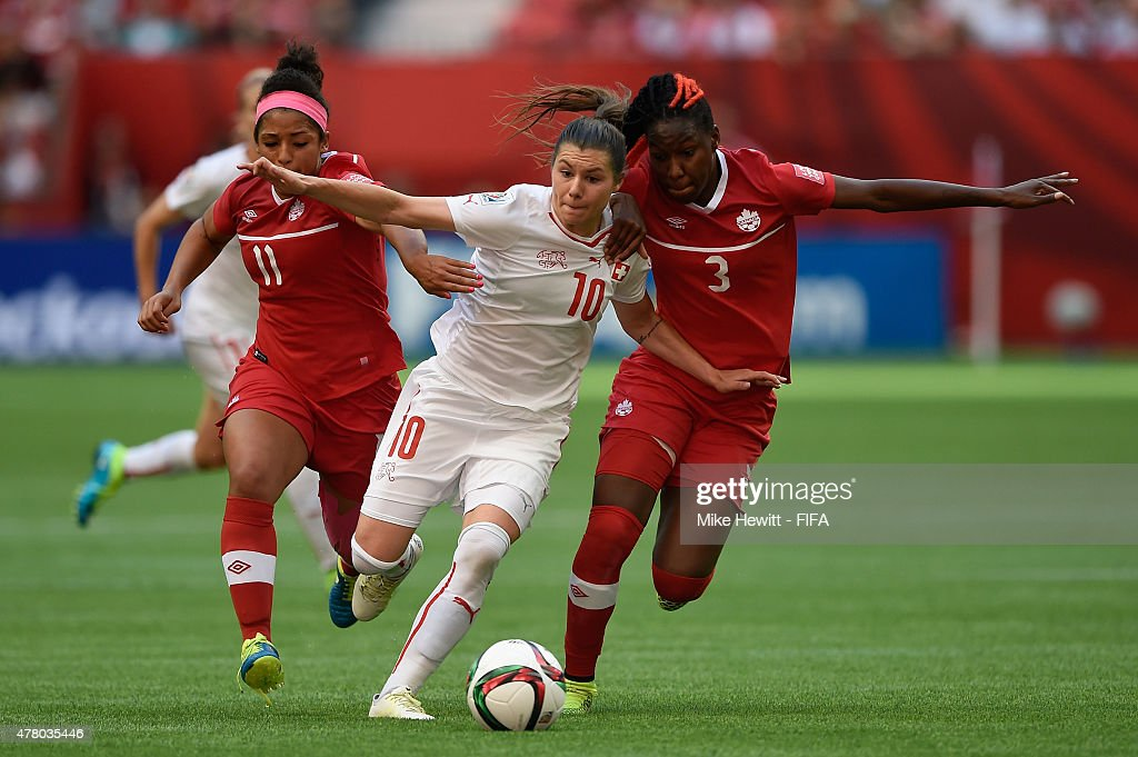 Ramona Bachmann of Switzerland is sandwiched by Desiree Scott (L) and Kadeisha Buchanan of Canada during the FIFA Women's World Cup 2015 Round of 16 match between Canada and Switzerland at BC Place Stadium on June 21, 2015 in Vancouver, Canada.