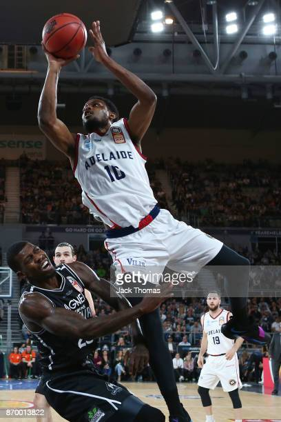 Ramone Moore of the Adelaide 36ers lays the ball up over Casey Prather of Melbourne United during the round five NBL match between Melbourne United...