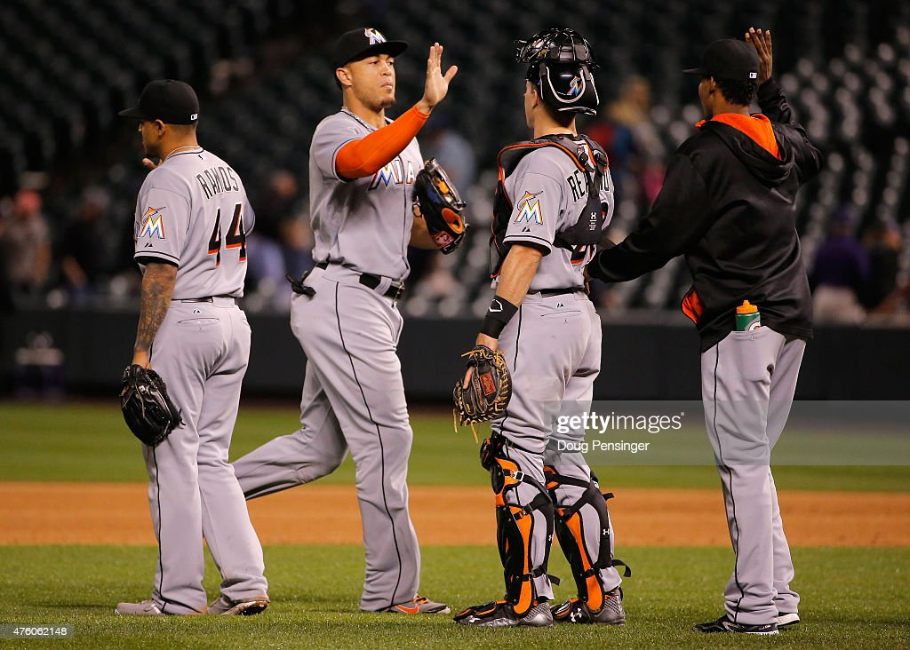 A.J. Ramos #44, Giancarlo Stanton #27 and J.T. Realmuto #20 of the Miami Marlins celebrate their 6-2 victory over the Colorado Rockies at Coors Field on June 5, 2015 in Denver, Colorado.