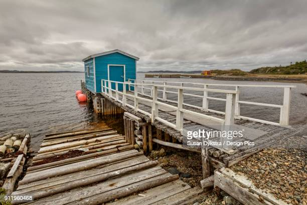 A ramp leading to a blue fishing shed and boat launch along the Atlantic coastline