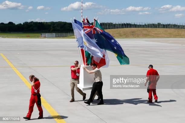 Ramp workers move flags just before US President Donald J Trump and the first lady Melania Trump arrive at Hamburg Airport for the Hamburg G20...
