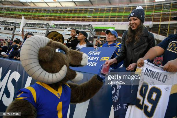 Rampage the Los Angeles Rams mascot hands a phone to a young fan after taking a photo before playing the San Francisco 49ers at Los Angeles Memorial...