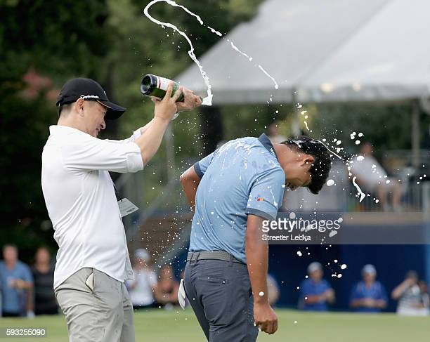 Rampert Sim pours champagne on Si Woo Kim after winning the Wyndham Championship during the final round at Sedgefield Country Club on August 21, 2016...