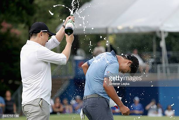 Rampert Sim pours champagne on Si Woo Kim after winning the Wyndham Championship during the final round at Sedgefield Country Club on August 21 2016...