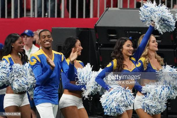 Rams cheerleader Quinton Peron walks onto the pitch with other cheerleaders during Super Bowl LIII between the New England Patriots and the Los...