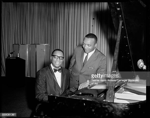 Ramsey Lewis seated at piano with Walt Harper leaning against it on stage at Pittsburgh Hilton for jazz workshop Pittsburgh Pennsylvania 1969